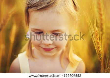 A cute blonde little girl in a wheat field on a sunny summer day close up - stock photo