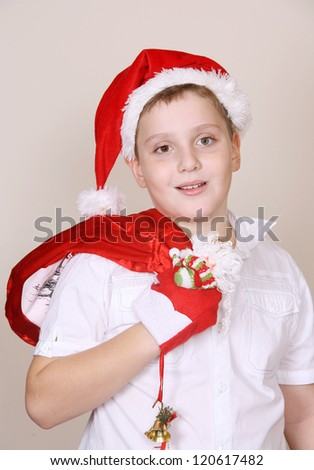 A cute boy in a red christmas hat and with holiday bag - stock photo