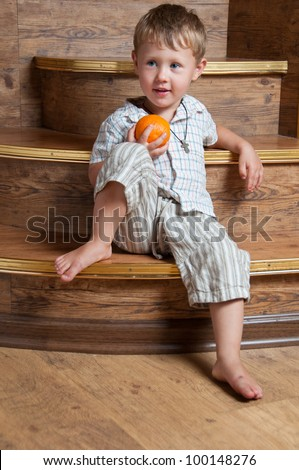A cute boy with an orange in his hand sitting on the steps. - stock photo