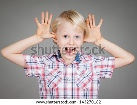 A cute cheeky young boy smiling and sticking his fingers in his ears and pulling a funny face. Isolated over white. - stock photo
