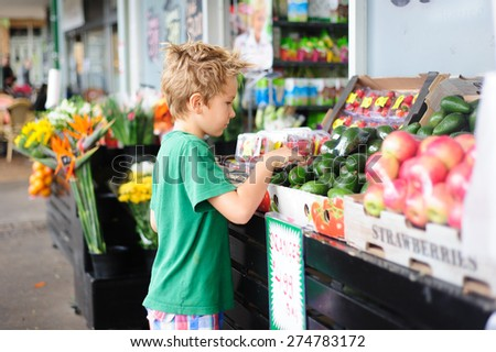 A cute child, primary school age boy picking avocado from a fruit stall while shopping at the shops - stock photo
