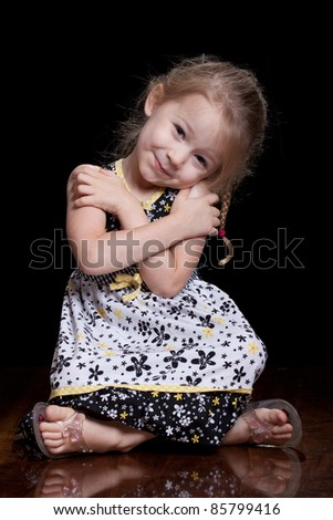 A cute child sits down and gives herself a hug.