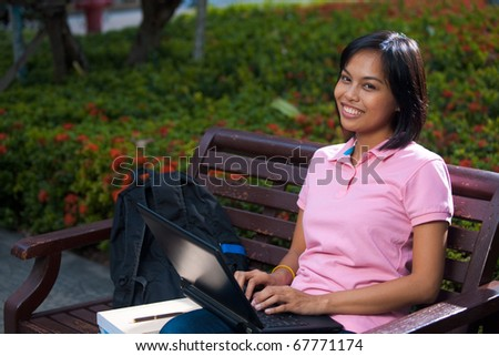 A cute college coed smiles and uses her laptop on a university campus bench.  20s female Asian Thai model of Chinese descent. - stock photo