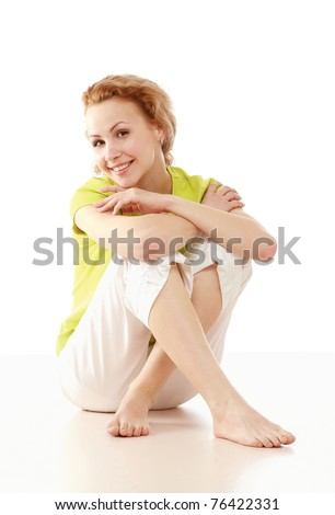 A cute college girl sitting on the floor - stock photo