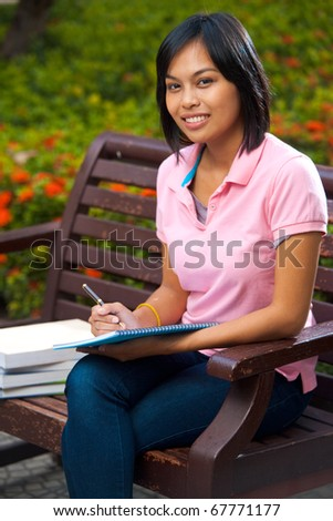 A cute college student smiles while studying on a university campus bench surrounded by flowers.  20s female Asian Thai model of Chinese descent. - stock photo