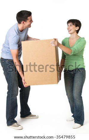 A cute couple moving a box together.  They are smiling.  Vertically framed shot.