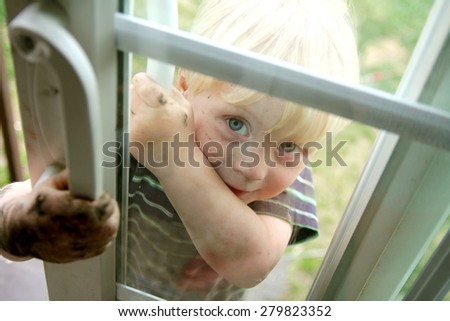A cute dirty toddler child is smiling as he peeks in the window of a sliding glass door from outside. - stock photo