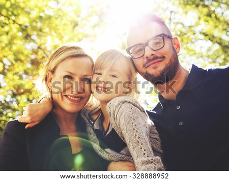a cute family posing in a park toned with a retro vintage instagram filter effect app or action - stock photo