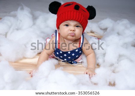 a cute frowning baby girl in studio - stock photo