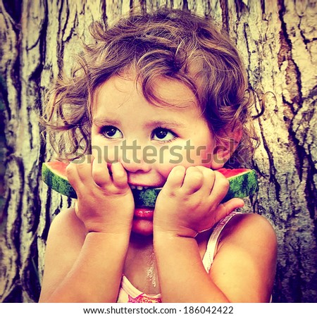 a cute girl eating watermelon done with a retro vintage instagram filter - stock photo