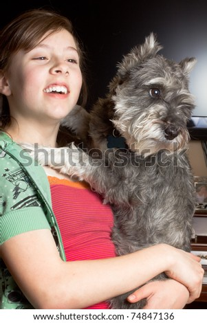 A cute girl holding a happy Miniature Schnauzer dog. - stock photo