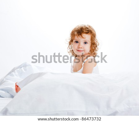 A cute girl in white sitting in bed - stock photo