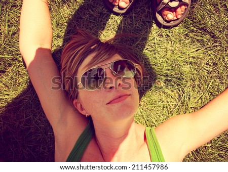 a cute girl laying on the grass in a snapshot like photo toned with a retro vintage instagram filter  - stock photo
