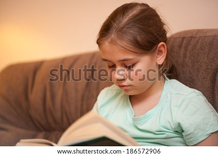 A cute girl reading a book at home on the couch - stock photo