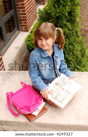 A cute girl sitting on the steps of her school reading a book - stock photo