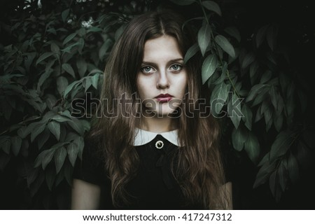 A cute goth girl wearing black dress stands amongst autumnal trees.Beautiful witch in the woods.Sad lonely girl.Beautiful eyes.  - stock photo