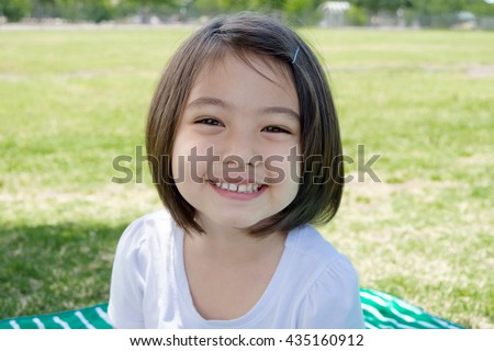 A cute happy little girl sitting smiling and laughing at park with light green grass background in summer time - stock photo