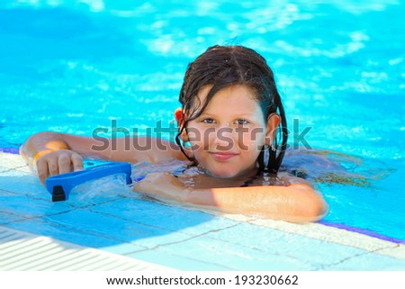 A cute happy young girl child relaxing on the side of a swimming pool - stock photo