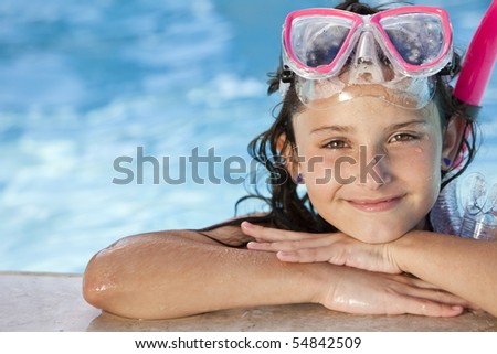 A cute happy young girl child relaxing on the side of a swimming pool wearing pink goggles and snorkel - stock photo