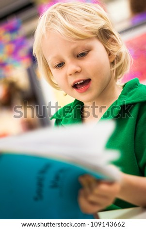 A cute happy young school boy reading a book in a class room. - stock photo