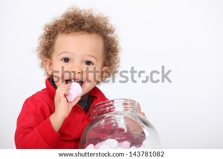 A cute kid eating marshmallow - stock photo