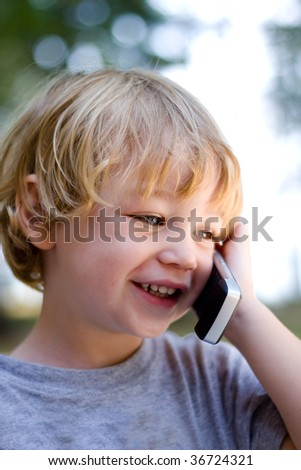 A cute laughing young boy talking on a mobile phone. - stock photo