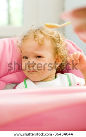 A cute little baby fed by her mother with a spoon, with a sad facial expression, she does not want to eat. - stock photo