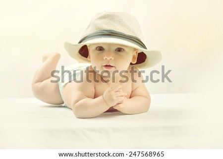 A cute little baby is looking into the camera and is wearing a white hat. The baby could be a boy or girl