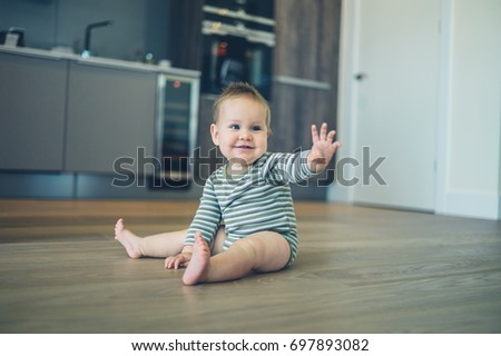 A cute little baby is sitting on the kitchen floor and is waving