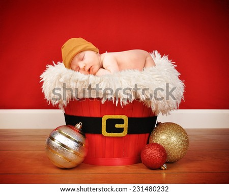 A cute little baby is sleeping in a santa wooden basket with a red background for a portrait or christmas concept.