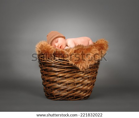 A cute little baby is sleeping in a wooden basket with brown fur and is wearing a hat. The baby could be a boy or girl on a isolated gray photography backdrop for a parenting or love concept.