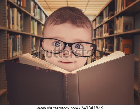 A cute little baby is wearing eye glasses and reading a library book for an education or learning concept. - stock photo