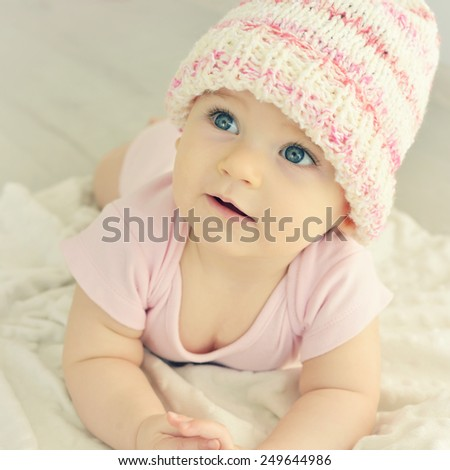A cute little baby. Newborn baby girl in pink knitted hat. Parenting or love concept. Toned photo. - stock photo