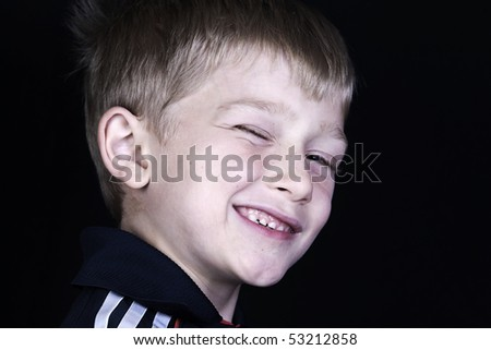 a cute little blonde boy winks at the camera