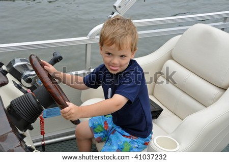 a cute little boy drives a boat while sticking out his tongue - stock photo