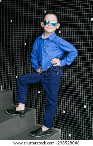 A cute little boy is dressed in a blue shirt and trousers. He wears sunglasses.Studio shot - stock photo