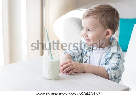A cute little boy is eating candy and drinking milk. Health. Happy child. Breakfast. A little boy is sitting at the table.