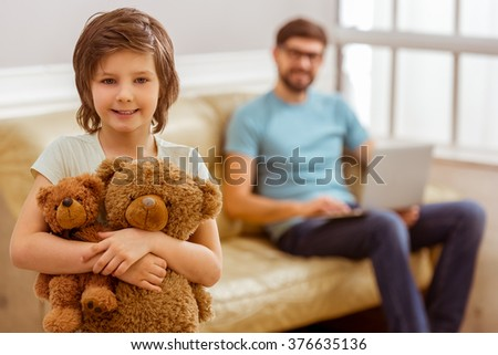 A cute little boy looking in camera and hugging teddy bears, in the background his father using a laptop while sitting on a sofa - stock photo