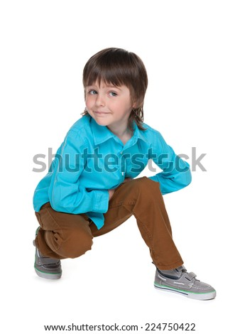 A cute little boy sits on the white background