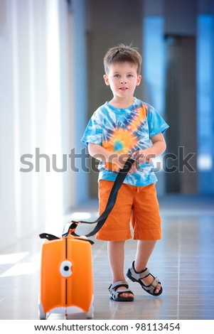 A cute little boy with orange suitcase at airport - stock photo
