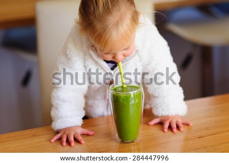 A cute little girl drinking healthy green smoothie with a straw out of the glass in the kitchen