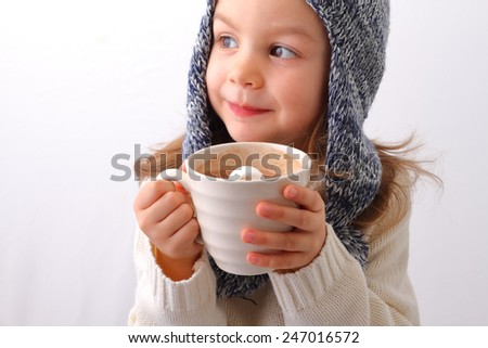A cute little girl drinking hot chocolate with marshmallow - stock photo