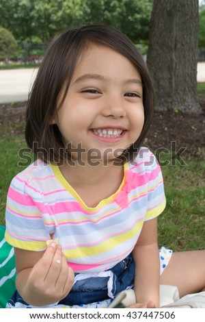 A cute little girl eating chips while having picnic in park with green background - stock photo