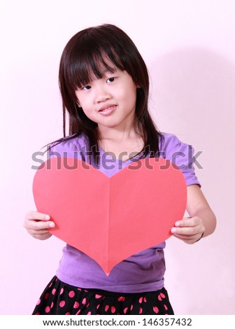 A cute little girl holding a heart shape paper
