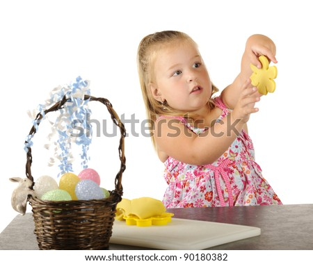 A cute little girl holding up the yellow flower she cut out of kiddie dough for Easter. - stock photo