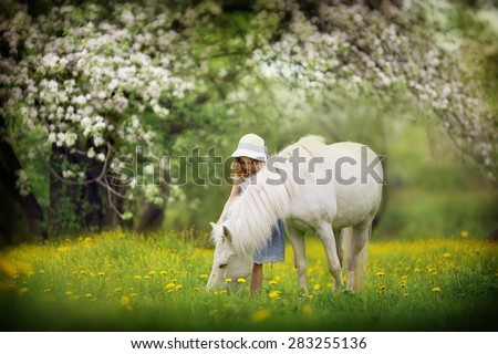 A cute little girl in a white hat caressing her little pony in the blooming garden on a sunny spring day. Kids in the country.  - stock photo