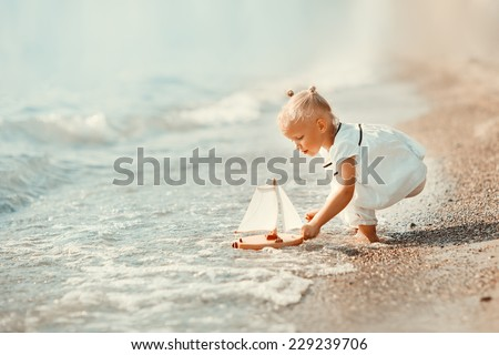 A cute little girl in white clothes playing with a toy ship on the beach on a warm sunny summer day. Holidays at sea. Funny kids - stock photo