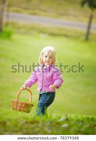 A cute little girl is holding a basket at the top of a hill.  Selective focus has been used.  The little girl looks relaxed and is looking at the camera. - stock photo