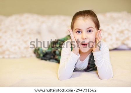 A cute little girl lying on the floor while pulling a face - stock photo