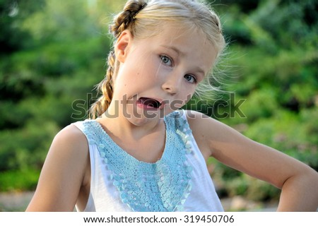 A cute little girl making funny face outdoor - stock photo